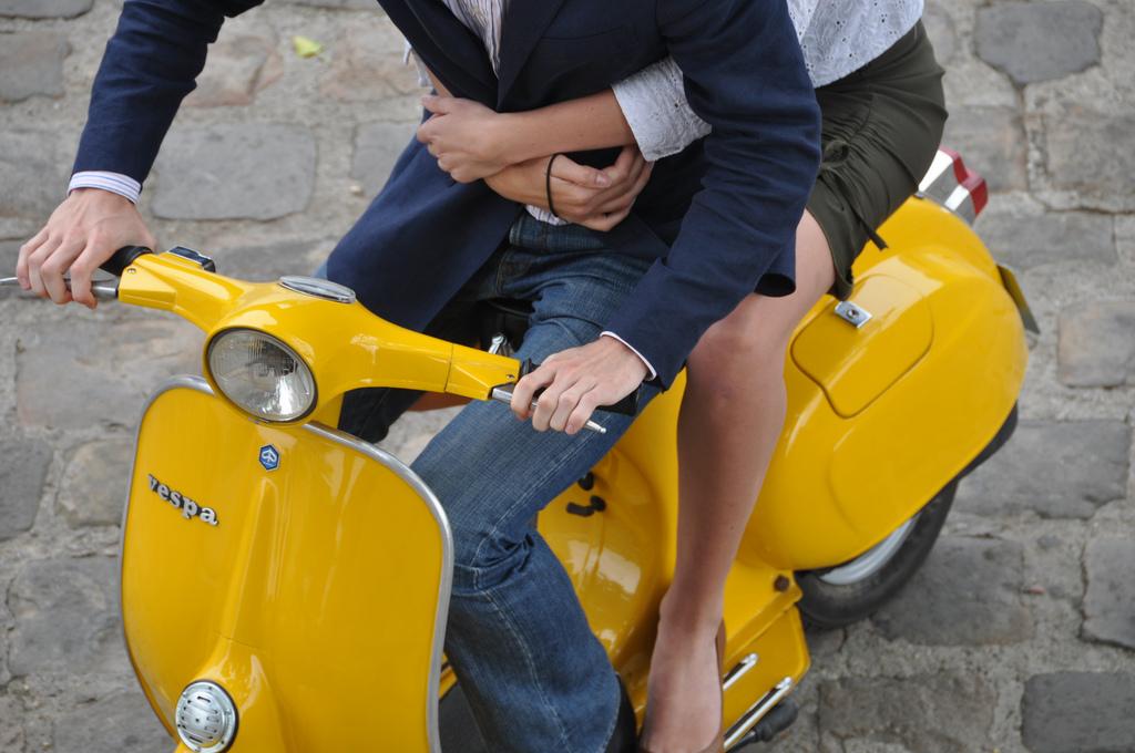 męzczyzna i kobieta na żółtym skuterze vespa